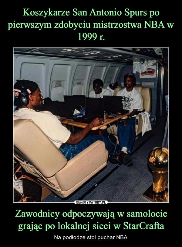 Zawodnicy odpoczywają w samolocie grając po lokalnej sieci w StarCrafta – Na podłodze stoi puchar NBA